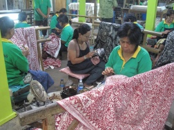 Women working in a factory workshop creating batik using canting.