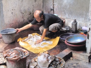 Aprat preparing Tatang's batik for Napthol dyeing.