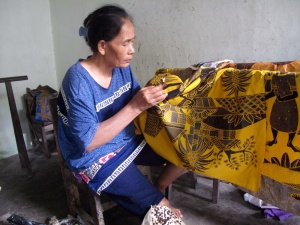 Woman carefully waxing the palm leaves of this design.
