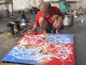 A cotton batik being  re-waxed by Aprat.