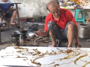 Aprat Koeswadji working on silk, using a mixture of beeswax and tree resin,