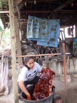 Mufida dyeing a batik with natural dye made from Mahogany bark.