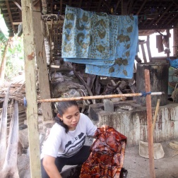 Mufida dyeing a batik with natural dye made from Mahogany bark.