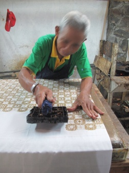 Man working in small factory workshop using the cap wax printing technique.