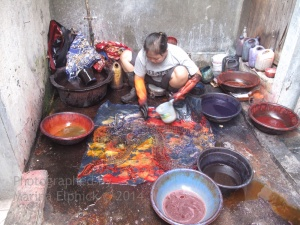 Mrs Poniyem dyeing Aprat Koeswadji's batik in his studio/ dye area