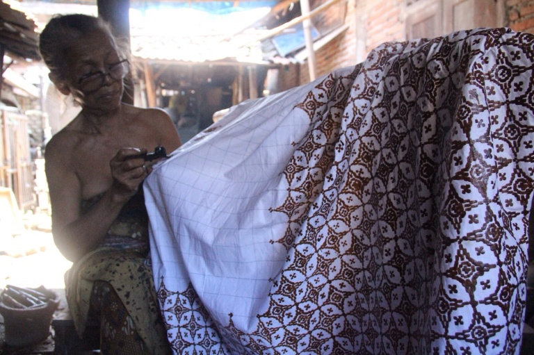 Woman creating Nitik using her customised canting to wax the fabric with a dark mix of beeswax and pine resin.