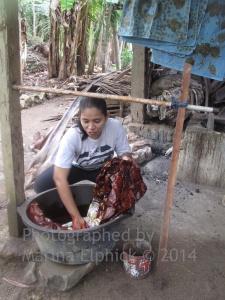Mufidah dyeing her batik in natural red Mahogany dye