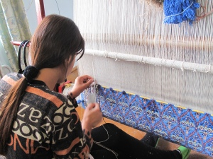Lady working on a traditional design on silk carpet made with naturally dyed silk threads.