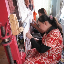 Women working on a traditional design on silk carpet made with naturally dyed silk threads.