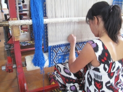 Lady working on a classic design on silk carpet made with naturally dyed silk threads.