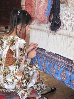Lady working on an original design on silk carpet made with naturally dyed silk threads.