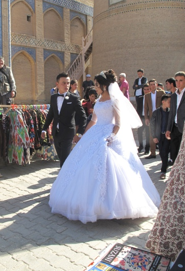 A modern wedding, couple at Islam-Khadja Madrasah, Khiva, Uzbekistan.